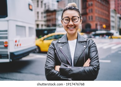 Half length portrait of joyful female tourist in optical eyewear and terndy leather jacket posing at urban street, funny Japanese hipster girl with crossed hands smiling at camera during vacations