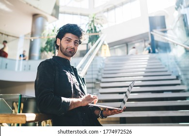 Half length portrait of Middle Eastern entrepreneur holding modern laptop computer in hand and looking at camera, confident IT professional with digital netbook for developing posing indoors