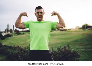 Half length portrait of muscular athletic man showing pumped up arms biceps during cardio training in park, Caucasian bodybuilder feeling confidence and power strength proud of own sportive goals