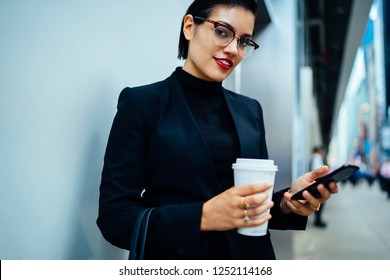 Half length portrait of positive female proud ceo in formal wear holding takeaway cup with hot caffeine beverage and smartphone gadget and looking at camera while waiting partner on urban setting