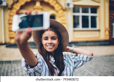 Half length portrait of positive female blogger traveller in stylish hat smiling at camera while shooting video of herself and showplaces on smartphone camera during weekend trip in architectural city