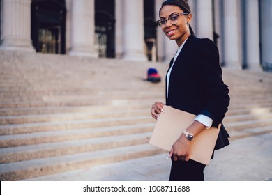 Half length portrait of positive woman executive dressed in elegant suit standing in city outdoors. Cheerful African American lawyer holding folder with documents standing against courthouse building