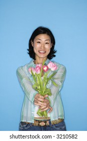 Half length portrait of pretty Asian mid adult woman holding flowers on blue background.