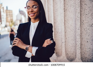 Half length portrait of prosperous African American young woman lawyer in elegant wear crossing hands while standing near office building. Successful dark skinned businesswoman smiling for the camera