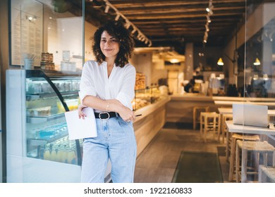 Half length portrait of prosperous manager of local bakery smiling at camera during work day in franchise takeaway cafe, happy woman with paper statistics enjoying time for improve own coffeehouse