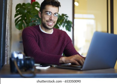 Half length portrait of smiling it developer working remotely at modern computer while looking at camera.Bearded freelancer in eyeglasses typing text information on digital laptop sitting in coworking