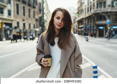 Half length portrait of a smiling hipster girl dressed in trendy street outfit holding take away coffee cup in hand and looking at camera while strolling outdoors. Student girl walking down the street