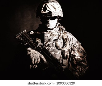 Half length portrait of special operations forces soldier, private military company guard in helmet, mask and uniform armed machine gun looking at camera. Contrast light, brown tone, black background