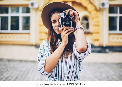 Half length portrait of stylish female tourist in trendy hat focusing and making photo on vintage camera with modern lense standing on architectural promotional background of downtown