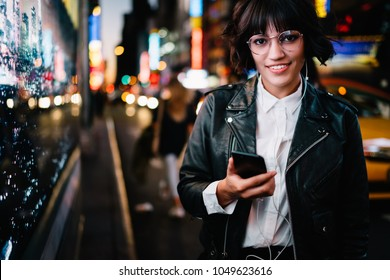 Half length portrait of stylish hipster girl in spectacles and earphones smiling at camera while listening song from music app installed on phone during night walk in metropolis with neon illumination