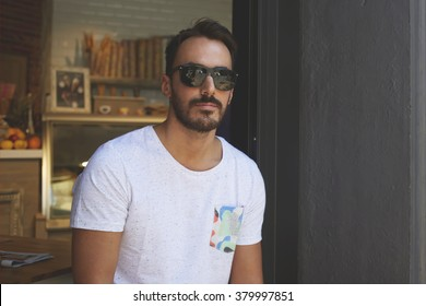 Half length portrait of stylish young business owner in dark sunglasses posing near own grocery store, confident handsome rich male resting near bakery during recreation time in warm summer season