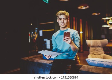 Half length portrait of successful Chinese hipster guy holding paper documents and smartphone gadget for wireless browsing, youthful Japanese man with modern mobile phone smiling at camera
