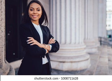 Half length portrait of successful happy businesswoman with dark skin crossed arms smiling at camera.Prosperous African American financial manager dressed in formal wear standing near copy space