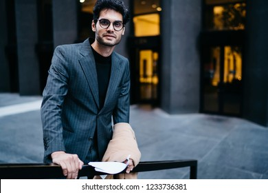 Half length portrait of successful male traer with paper documentation in hands smiling at camera while standing outdoors in urban setting.Positive lawyer laughing near office building