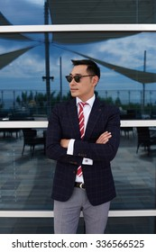 Half length portrait of successful man ceo dressed in corporate clothes standing with crossed arms near office building, young confident managing director resting after business meeting with partners