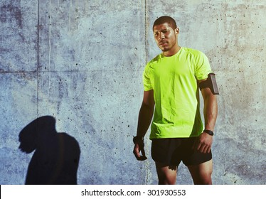 Half length portrait of sweaty man athlete resting after physical exercise while standing against cement wall background with copy space area for your text message or advertising, runner having a rest
