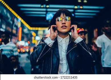 Half length portrait of trendy female millennial in electronic spectacles looking at camera during time for listening audio book and walk in metropolitan downtown, generation z in earphones