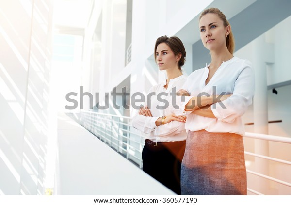 Half length portrait of a two female rivals with crossed arms standing side by side in office interior, team of skilled women partners of the company dissatisfied with the result of important meeting