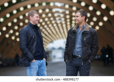 half length portrait of two young man in black jacket on background of lights installation main park alley, talking