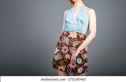 Half length portrait woman wearing cute dress. Halter top with fitted skirt. Woman is dancing. hips to her right. Studio shot with gray background.