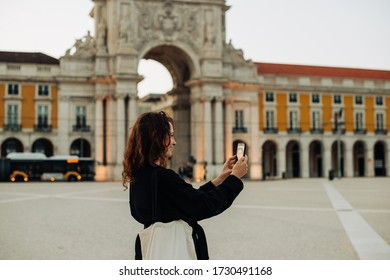 Half length portrait of a woman wearing black talking to friend using her smartphone, standing alone at Praca do Comercio, Commerce Square, in Lisbon, during partial lock down in Portugal
