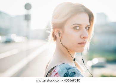 Half length portrait of young beautiful blonde woman outdoor in the city back light, listening music with earphones, looking in camera - music, relaxing, pensive concept - copy space left