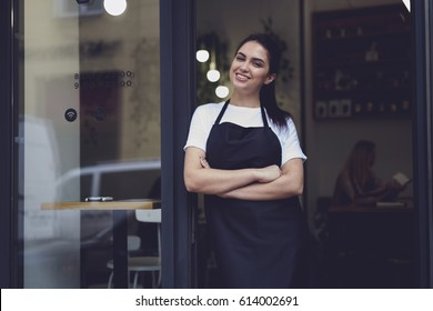 Half length portrait of young business woman waitress in black apron ready to attend new customers in her just opened coffee shop.Female owner of restaurant with smile standing near cafe door entrance