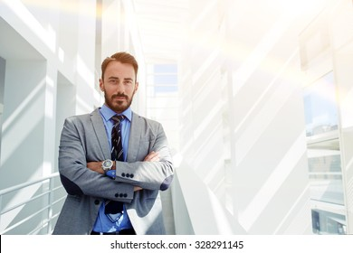 Half length portrait of young confident man manager standing with crossed arms in hall of his corporation, prosperous male leadership dressed in elegant luxury clothes relaxing after business meeting