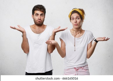 Half length portrait of young couple standing against white background shrugging their shoulders having uncertainty not knowing what to do. Pretty wife and her husband having doubts isolated