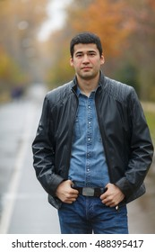 half length portrait of young dark-haired man in black jacket on avenue in park, hands on his belt