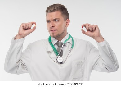 Half length portrait of young fair-haired doctor, holding in both hands two different pills, and looking suspiciously at one of them. Isolated on the white background