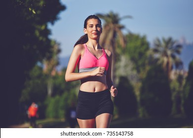 Half length portrait of young female jogger running in the park