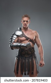 Half length portrait of young handsome muscular man gladiator in armour showing his thumb up isolated over grey background, concept of success, victory