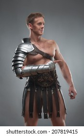 Half length portrait of young handsome muscular man gladiator in armour pointing aside isolated over grey background