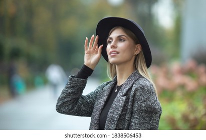 Half length portrait of young happy woman walking in the street.
