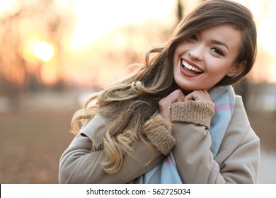 half length portrait of young happy woman walking in the street on sunset