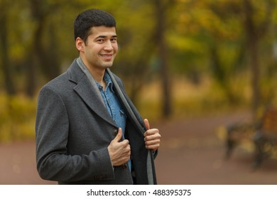 half length portrait of young man in gray coat, smiling and posing, side view