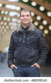half length portrait of young man in black jacket on background of lights installation main park alley, smiling