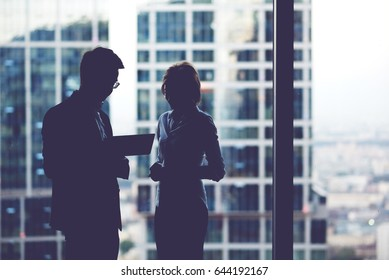 Half length portrait of young man and woman purposeful entrepreneurs watching information on digital tablet,two confident colleagues using touch pad during work break while standing in office interior