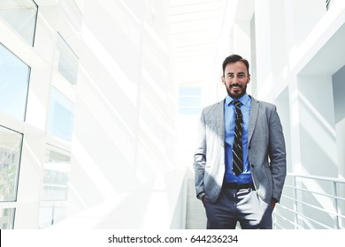 Half length portrait of a young smiling businessman dressed in corporate clothing with hands in pockets standing in modern space, handsome happy intelligent man in luxury suit relaxing after work day