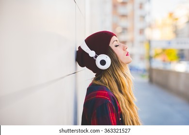 Half length profile portrait of young handsome caucasian blonde hair woman leaning against a wall, listening music with headphones, eyes closed - serene, enjoying, music concept