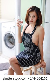half length of sexy and attractive asian woman, short hair wife in black and white sexy apron, no bra she sitting take a rest and drinking water while cooking in kitchen (lifestyle concept)