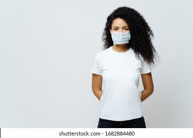 Half length shot of Afro American woman being on self isolation or quarantine, wears medical mask during coronavirus outbreak, listens news, tries not to spread virus, stays at home for long period