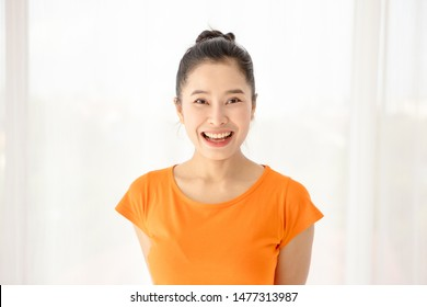 The half length shot of a beautiful Asian woman wearing a black hair bun, smiling at the camera happily. A simple portrait shot with natural light. Showing positive and friendly gestures.
