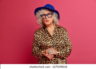 Half length shot of beautiful old woman wears blue hat, stylish shirt with leopard print, keeps lips rounded, wants to kiss family members, prepares for special occasion, isolated on pink background