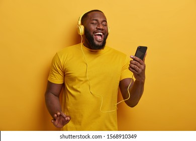 Half length shot of black guy listens music to chill, holds modern smartphone and wears headphones on ears, enjoys nice track, poses against yellow background. People, technology, lifestyle.
