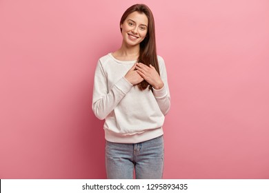 Half length shot of brunette cheerful young woman keeps hands on chest, demonstrates sign of gratitude and affection, has positive emotions, sincere smile, isolated over pink studio background.