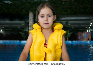 A half length shot of a little cute girl in a swim device at the water park background. A little girl looks at camera staying in indoor pool of an aquapark. A little girl after swimming in aquapark.