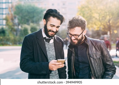 Half length of two young bearded modern businessman using smart phone handhold looking downward the screen - technology, business, work concept