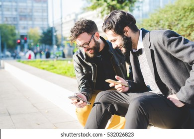 Half length of two young bearded modern businessman using smart phone handhold looking downward the screen smiling - technology, business, work concept